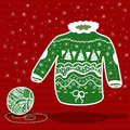 Green knitted christmas sweater and a ball of yarn on red background Stock Image