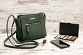 Green ladies handbag, phone, eyeshadow palette and a lipstick on a wooden background. fashion concept Royalty Free Stock Photo