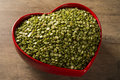 Green lentils inside a heart pot on wood background. Edible raw pulses of the legume family
