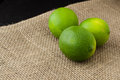Green limes on a jute table cloth Royalty Free Stock Photo