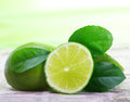 Green limes with leaves on wooden background Stock Images