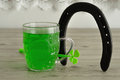 Green liquid in a beer mug displayed with a horseshoe Royalty Free Stock Photo