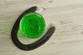 Green liquid in a beer mug  with a horseshoe Royalty Free Stock Photo