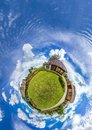 Green little planet panorama with architecture, soft blue sky and white clouds. Buildings at summer. Planet Earth.
