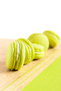 Green macaroons arranged diagonally on wooden table lie in a row shallow focus Stock Photo