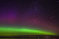 Green, magenta and purple aurora borealis with meteor over a lake in North Dakota Royalty Free Stock Photo