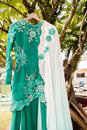Green malay wedding dress hanging on tree Royalty Free Stock Photos