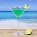 Green martini cocktail drink on the beach while vacation Royalty Free Stock Photo