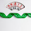 Green measuring tape on weight scale. Dieting Royalty Free Stock Photo