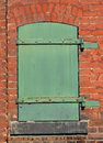 Green metal door in a brick wall old worn and weathered small closed solid the of an old factory Royalty Free Stock Photos