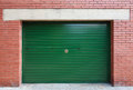 Green metal garage gate in red brick wall background texture Stock Images
