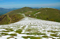 Green mountain ridge with snowfields of the spring pyrenees a crest is covered in Royalty Free Stock Photography