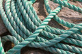 Green naval rope lies on the stone coast Stock Image
