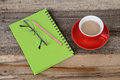 Green notebook and hot coffee a cup of on wooden table Stock Images