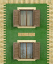 Green old house with two wooden window with facing bricks rendering Stock Image