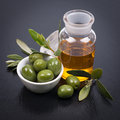 Green olives olive oil and on a slate Royalty Free Stock Photo