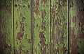 Green paint peeling from a wooden panel door Royalty Free Stock Photo