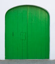 Green painted door with hatch and rounded top on whitewashed wall majorca spain Stock Images