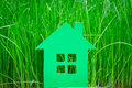 Green paper house on spring grass Royalty Free Stock Images