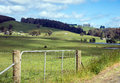 Green pastures barbed wire fence and gate in front of and rolling hills Royalty Free Stock Image