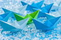 Green peace fleet of blue origami paper ships on blue water like background surrounding a green one waterlike Royalty Free Stock Photos