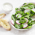 Green peas, radish and baby spinach salad on ceramic plate on a light background. Royalty Free Stock Photo