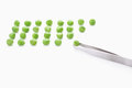 Green peas with tweezer on white background Stock Photography