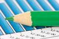 Green pencil on financial graphs Royalty Free Stock Photo