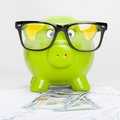Green piggy bank over stock market chart with 100 dollars banknote - 1 to 1 ratio Royalty Free Stock Photo