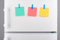 Green, pink, yellow notes attached with stickers on refrigerator Royalty Free Stock Photo