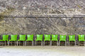 Green plastic chairs in raw near a wall in a salt mine Stock Image