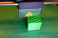3D printer with green plastic cube