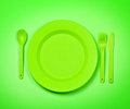 Green plastic disposable tablewar bright tableware plates and forks on bright background Stock Photos