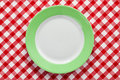 Green plate on checkered tablecloth Stock Photo