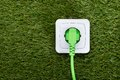Green plug in outlet on grass Royalty Free Stock Photo