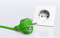 Green plug and socket ecological european disconnected lies on the ground in front of a white Royalty Free Stock Photography