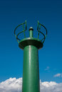 Green position light at the harbor entrance against a blue sky Royalty Free Stock Photo