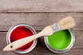 Green and red paint in the bank with brush on the old wooden background with copy space for your text. Top view