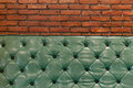 Green retro couch in a living room with bricks wall behind Royalty Free Stock Photo