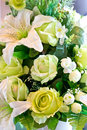 Green rose and white lily artificial flowers bunch close up of Stock Images