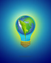 Green seedling with water & earth in light bulb on blue Royalty Free Stock Photo