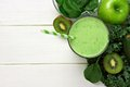 Green smoothie above view with ingredients against white wood Royalty Free Stock Photo