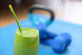 Green smoothie and dumbbells weights at the gym on yoga mat fitness concept clean eating detox with vegetable spinach Stock Photos