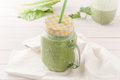 Green smoothie in a glass jar with lid and a straw Royalty Free Stock Photo