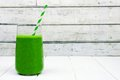 Green smoothie in a glass with straw over white wood Royalty Free Stock Photo