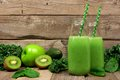 Green smoothie in with kale, avocado, spinach, apple and kiwi against rustic wood Royalty Free Stock Photo