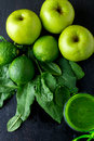 Green smoothie near ingredients for it on black wooden background. Apple, lime, spinach. Detox. Healthy drink. Top view. Royalty Free Stock Photo