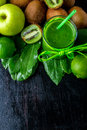 Green smoothie near ingredients for it on black wooden background. Apple, lime, spinach, kiwi. Detox. Healthy drink. Top view. Cop Royalty Free Stock Photo