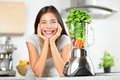 Green smoothie woman making vegetable smoothies with blender healthy eating lifestyle concept portrait of beautiful young Stock Photo