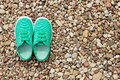Green sneakers on a background of small stones pair shoes Stock Image